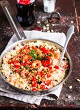 Couscous with fried prawns, mixed vegetables, pine nuts served in a cooking pan on a wooden table, selective focus. Traditional ea. Stern meal. Summer picnic stock images