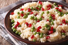 Couscous with green peas and pomegranate close-up. Horizontal Stock Image