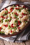 Couscous with green peas and pomegranate close-up. vertical Stock Photos