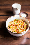 Couscous with green and red bell pepper, olive oil and sesame seeds in a bowl Royalty Free Stock Photography