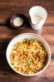 Couscous with green and red bell pepper, olive oil and sesame seeds in a bowl Royalty Free Stock Photo