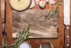 Couscous herb knife meat fork garlic and salt seasoning cutting board. Ingredients wooden rustic background close up top view. Couscous herb knife meat fork stock images