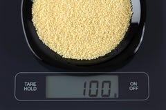 Couscous on kitchen scale Stock Photos