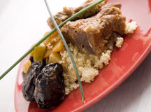 Couscous lamb. Sticky lamb with couscous, garnished with spring potatoes carrots and chickpeas Royalty Free Stock Photo