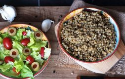 Couscous- och grönsallatsallad, tomater och oliv Arkivbild