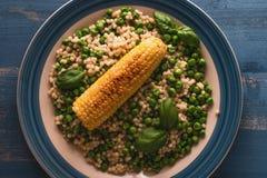 Couscous och havre på en platta med gröna ärtor och basilika arkivfoton