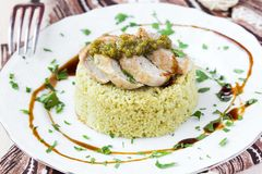 Couscous with pesto sauce, fried sliced pork, tasty dish Stock Photo
