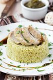 Couscous with pesto sauce, fried sliced pork, tasty dish Stock Image