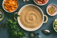 Couscous pot with cut vegetables ingredients in bowls , top view. Healthy vegetarian food Royalty Free Stock Images