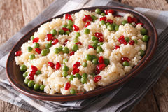Couscous salad with green peas and pomegranate close-up. horizon Royalty Free Stock Photos