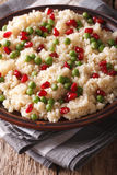 Couscous salad with green peas and pomegranate close-up. Vertica Royalty Free Stock Image