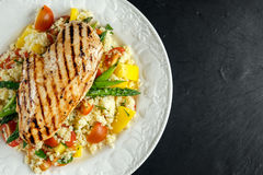 Couscous salad with grilled chicken and asparagus on white plate. stone table. healthy food Stock Photos