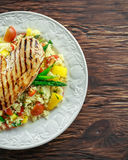 Couscous salad with grilled chicken and asparagus on white plate. wooden rustic table. healthy food Royalty Free Stock Photo