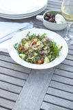 Couscous salad on outdoor table. Couscous salad with olives, Feta and wine on outdoor table setting Stock Image