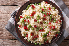 Couscous salad with peas and pomegranate closeup. horizontal top Royalty Free Stock Photos