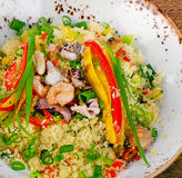 Couscous with vegetables and seafood  on wooden table. Royalty Free Stock Image