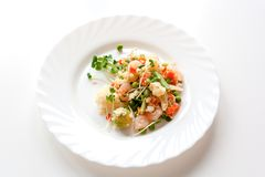 Couscous with vegetables, shrimp and radish on a white plate stock photos