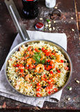 Couscous warm salad with red sweet bell pepper, eggplant, courgette, cherry tomatoes, roasted shrimps and dill in a pan Royalty Free Stock Photo