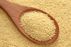 Couscous in a wooden spoon. On couscous background. Close-up Stock Photo