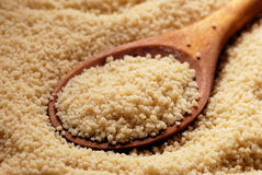 Couscous and wooden spoon Stock Photos