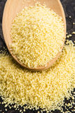 Couscous in wooden spoon stock image