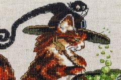 Cousez au point de croix la broderie avec le chat en chapeau, chaudron, crapaud, feu et potiron photos libres de droits