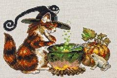 Cousez au point de croix la broderie avec le chat en chapeau, chaudron, crapaud, feu et potiron photo libre de droits