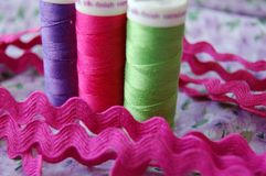 Cousez le temps ! Trois bobines colorées de fil dans pourpre, le rose et vert image libre de droits