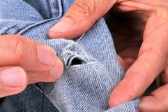 Cousez vers le haut de l'les jeans troués image libre de droits