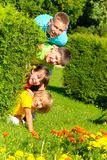 Cousins behind bush. Four siblings together in park Royalty Free Stock Images