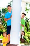 Cousins behind column. Four siblings together in park behind column Royalty Free Stock Photography
