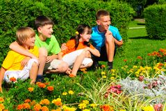 Cousins by flower garden. Four siblings together in park Stock Photography