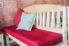 Coussin rouge sur le banc à l'intérieur en bois pour le siège avec le mur de briques image libre de droits