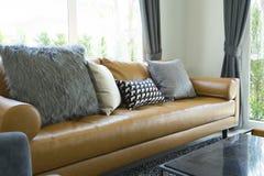 Coussin sur le sofa en cuir brun dans le salon image libre de droits