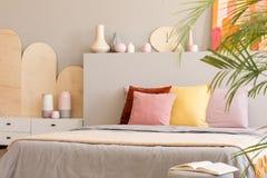Coussins colorés sur le lit avec la tête de lit à côté du coffret dans le gris photos stock