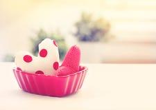 Coussins de coeur dans un plat rouge de coeur Image stock