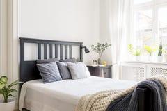 Coussins et couverture sur le lit avec la tête de lit noire dans l'inte de chambre à coucher photographie stock libre de droits