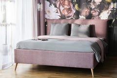 Coussins gris sur le lit rose dans l'intérieur lumineux de chambre à coucher d'hôtel avec photographie stock libre de droits