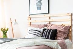 Coussins noirs et blancs placés sur le double lit avec le bedhea en bois photo libre de droits