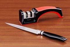 Couteau avec l'affûteuse de couteau sur la table en bois rendu 3d Photo libre de droits