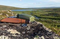 Couteau, boussole et carte sur la roche photo stock