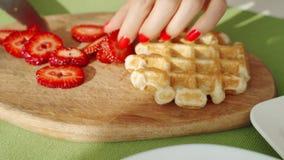 Couteau chez la main de la femme, coupant une fraise fra?che sur un conseil en bois Tir en gros plan banque de vidéos