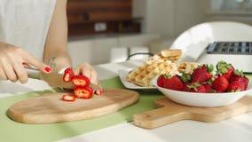Couteau chez la main de la femme, coupant une fraise fra?che sur un conseil en bois Tir en gros plan clips vidéos