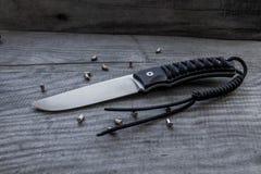 Couteau de chasse sur un fond en bois avec des boules Images libres de droits