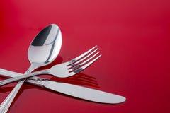 Couteau de cuillère de fourchette d'ustensiles sur le Tableau rouge Image stock