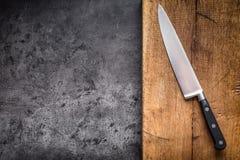 Couteau de cuisine sur le conseil concret ou en bois Image stock