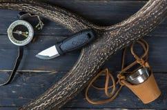 Couteau et boussole sur un fond noir Tasse de fer dans un cas en cuir Image stock