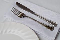 Couteau et fourchette autour de la plaque. Image libre de droits