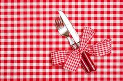 Couteau et fourchette avec l'arc à carreaux rouge Images stock