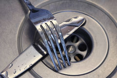 Couteau et fourchette dans le bassin de cuisine Image stock